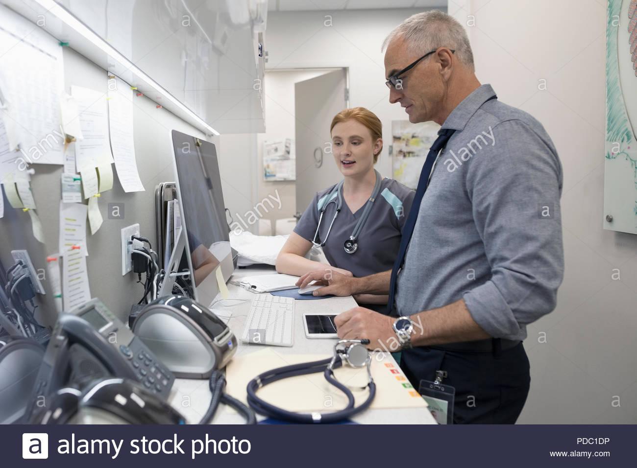 Médecin de sexe masculin et féminin à l'aide de l'infirmière dans une clinique de l'ordinateur Photo Stock
