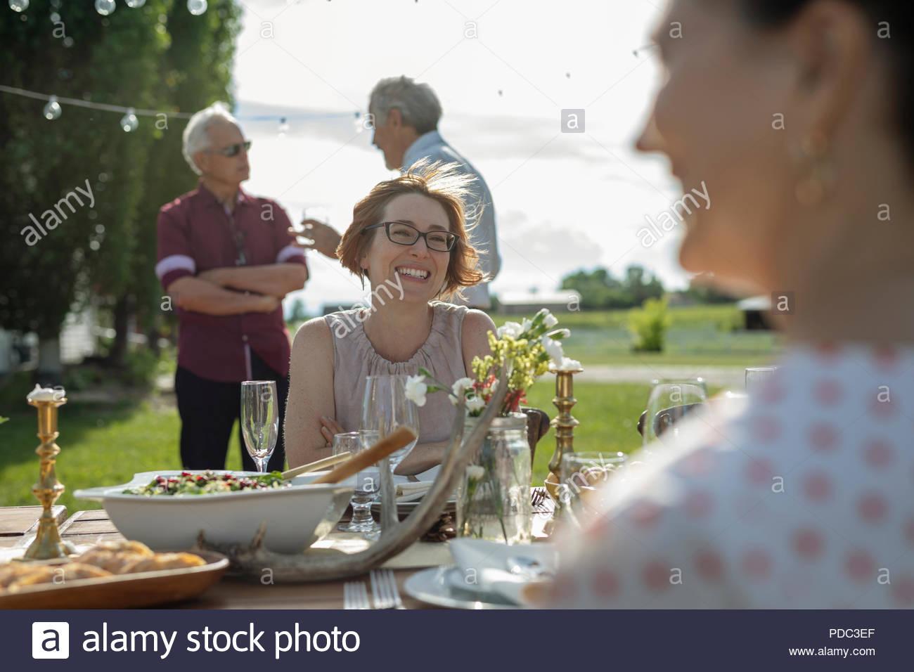 Smiling women enjoying déjeuner à table de patio ensoleillé Photo Stock