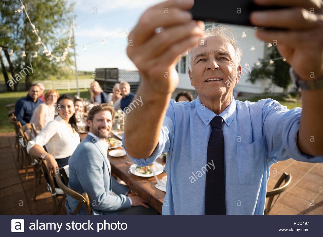 Senior man with camera phone selfies avec des amis à prendre parti à la retraite en milieu rural jardin ensoleillé Photo Stock