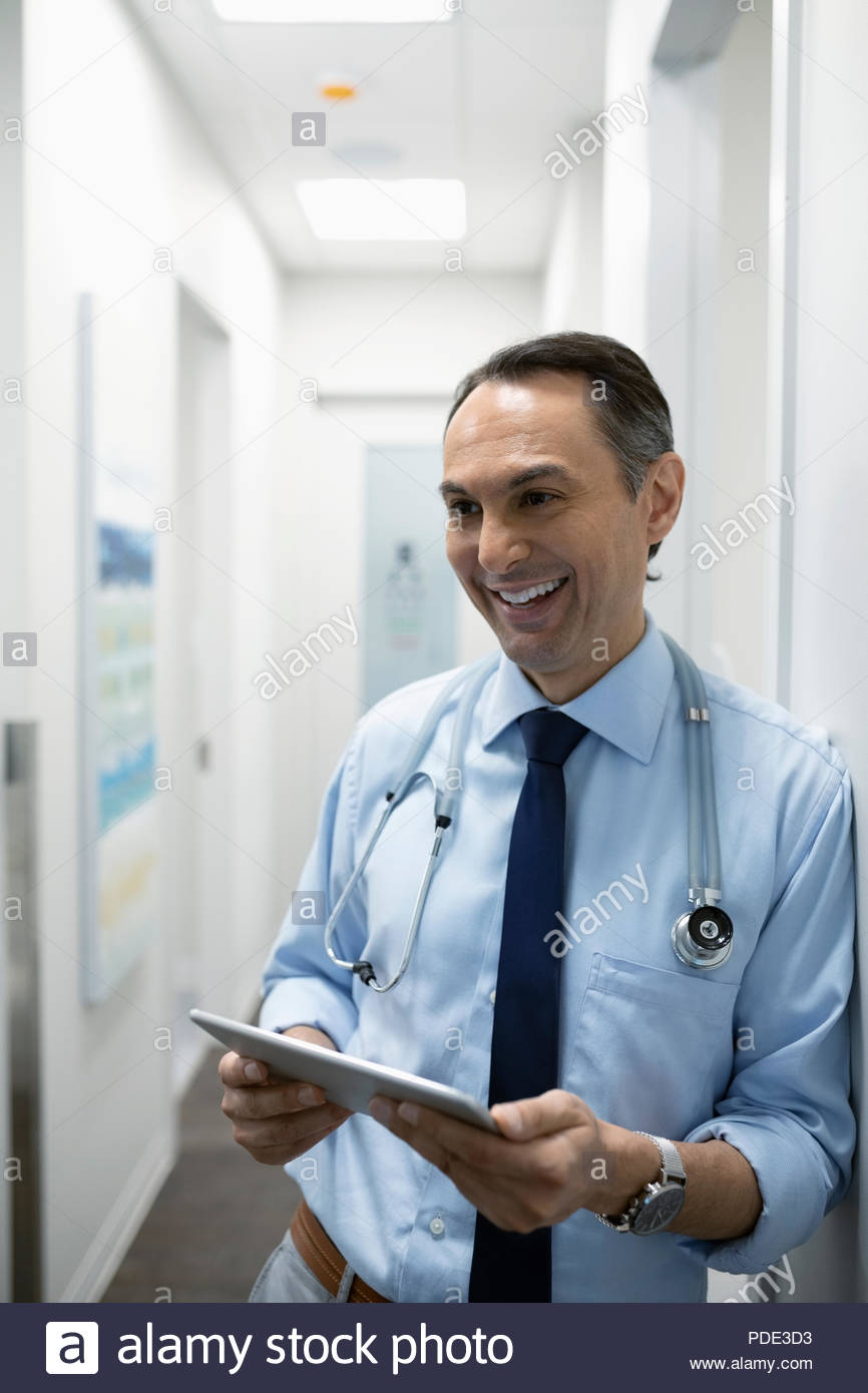 Smiling male doctor using digital tablet in corridor clinique Photo Stock
