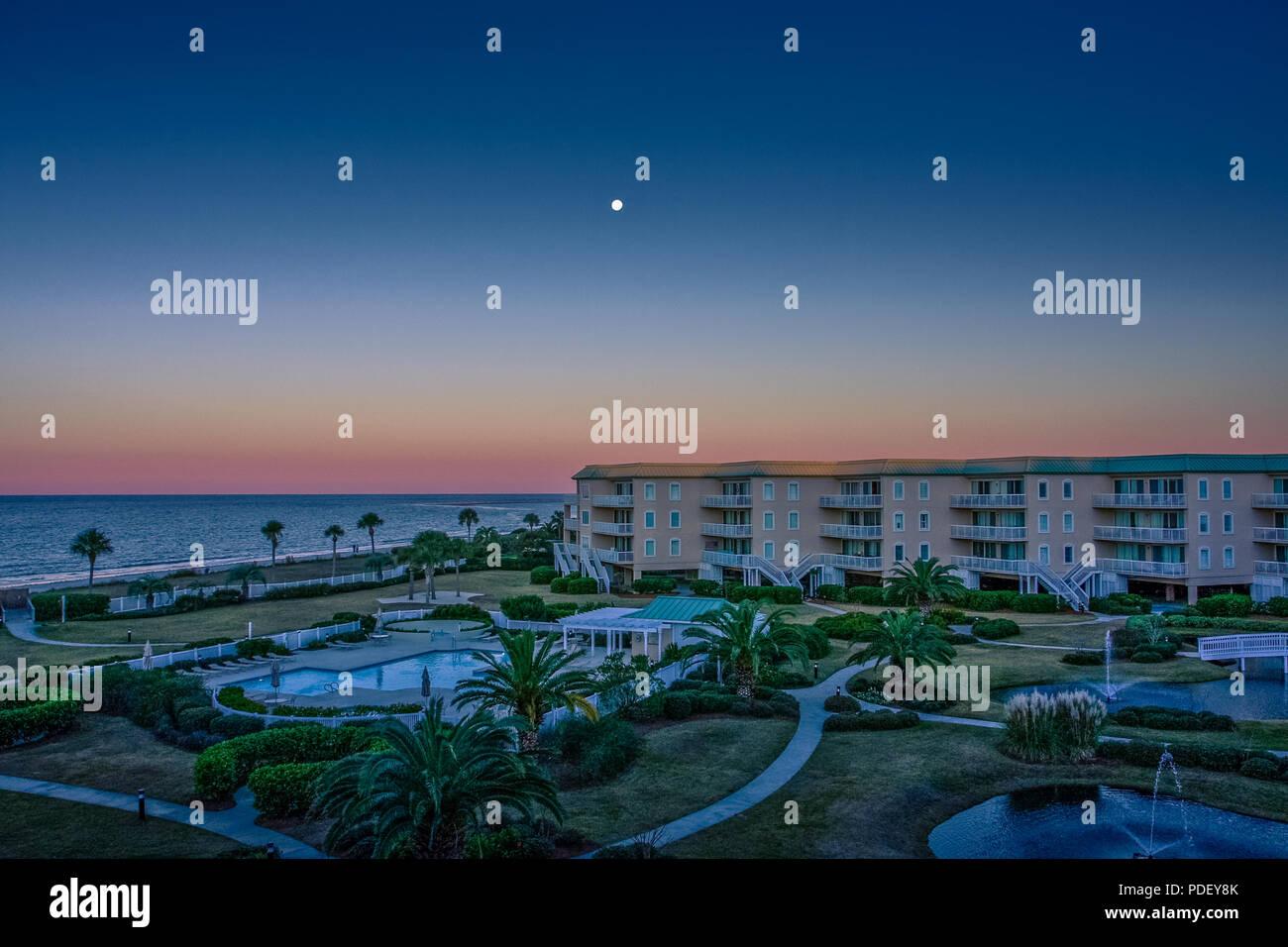 Une pleine lune dans un ciel clair crépuscule sur beach condos Banque D'Images