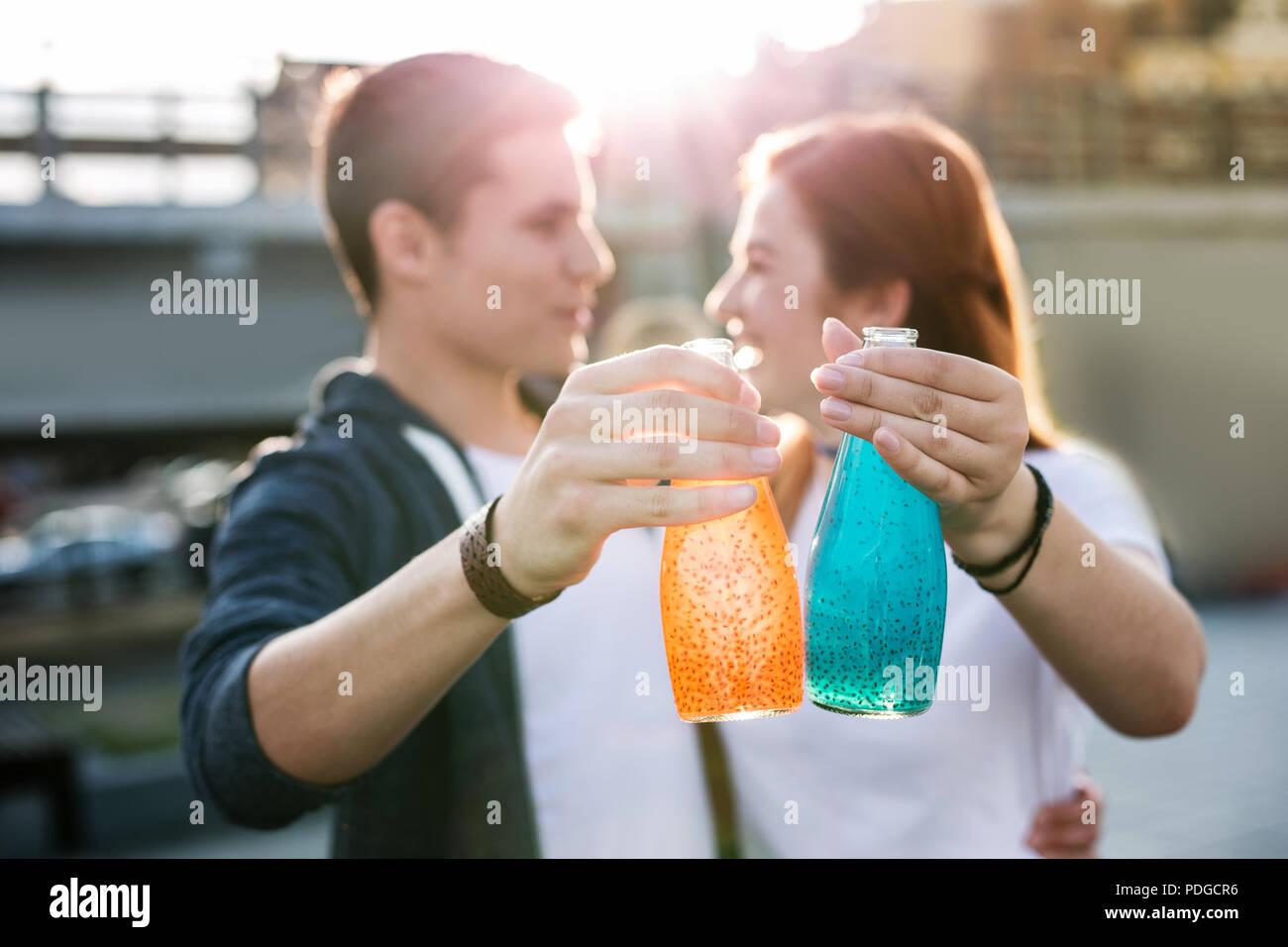 Bouteilles de boissons étant dans les mains de jeunes gens joyeux Photo Stock