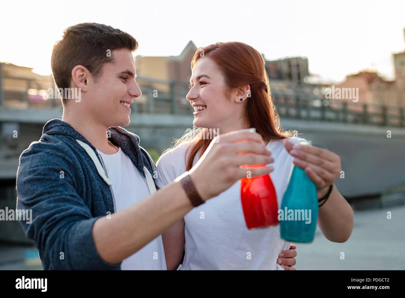 Heureux couple positif boire du jus si délicieux. Photo Stock