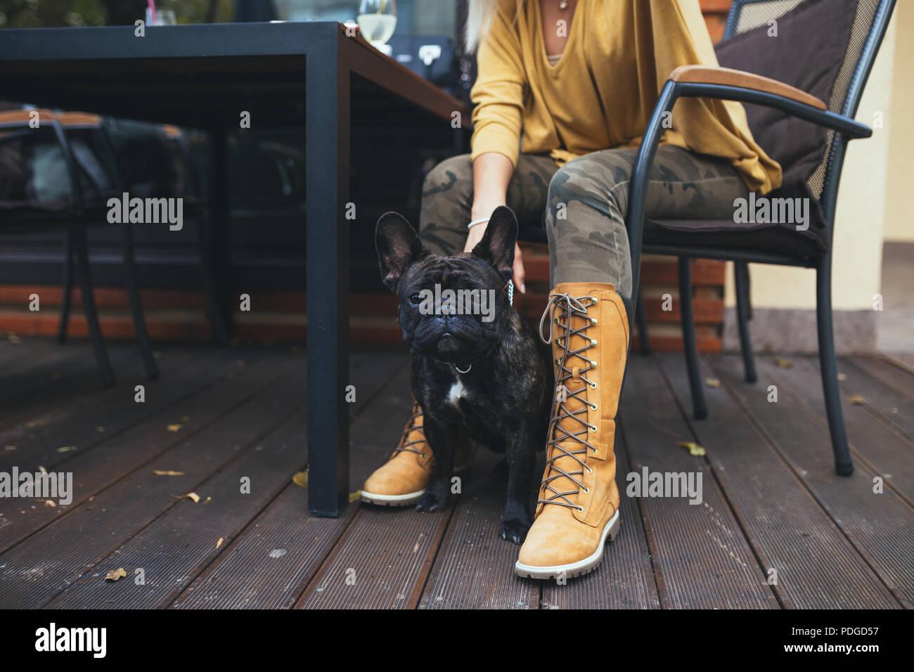 Belle et bonne blonde woman with tablet en bénéficiant d'un café bar avec son adorable bouledogue français. Photo Stock