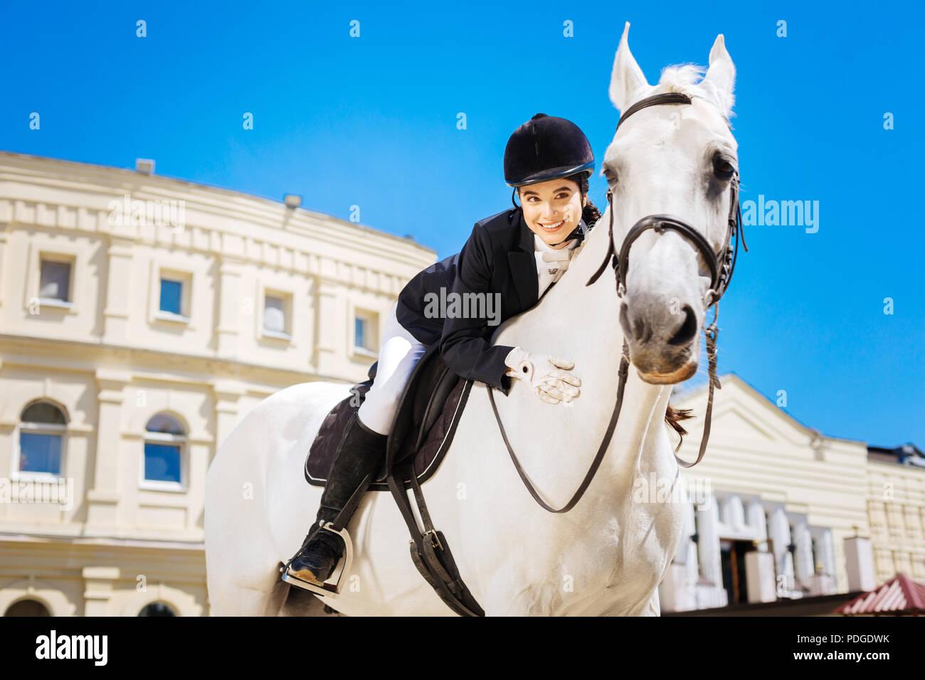 Black-eyed transmission rider femme appuyée sur son cheval blanc consacrée Photo Stock