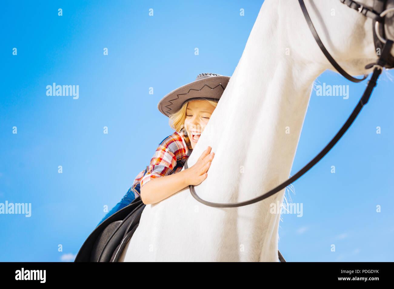 Aux cheveux blonds funny girl rire alors que son cheval Cheval blanc Photo Stock