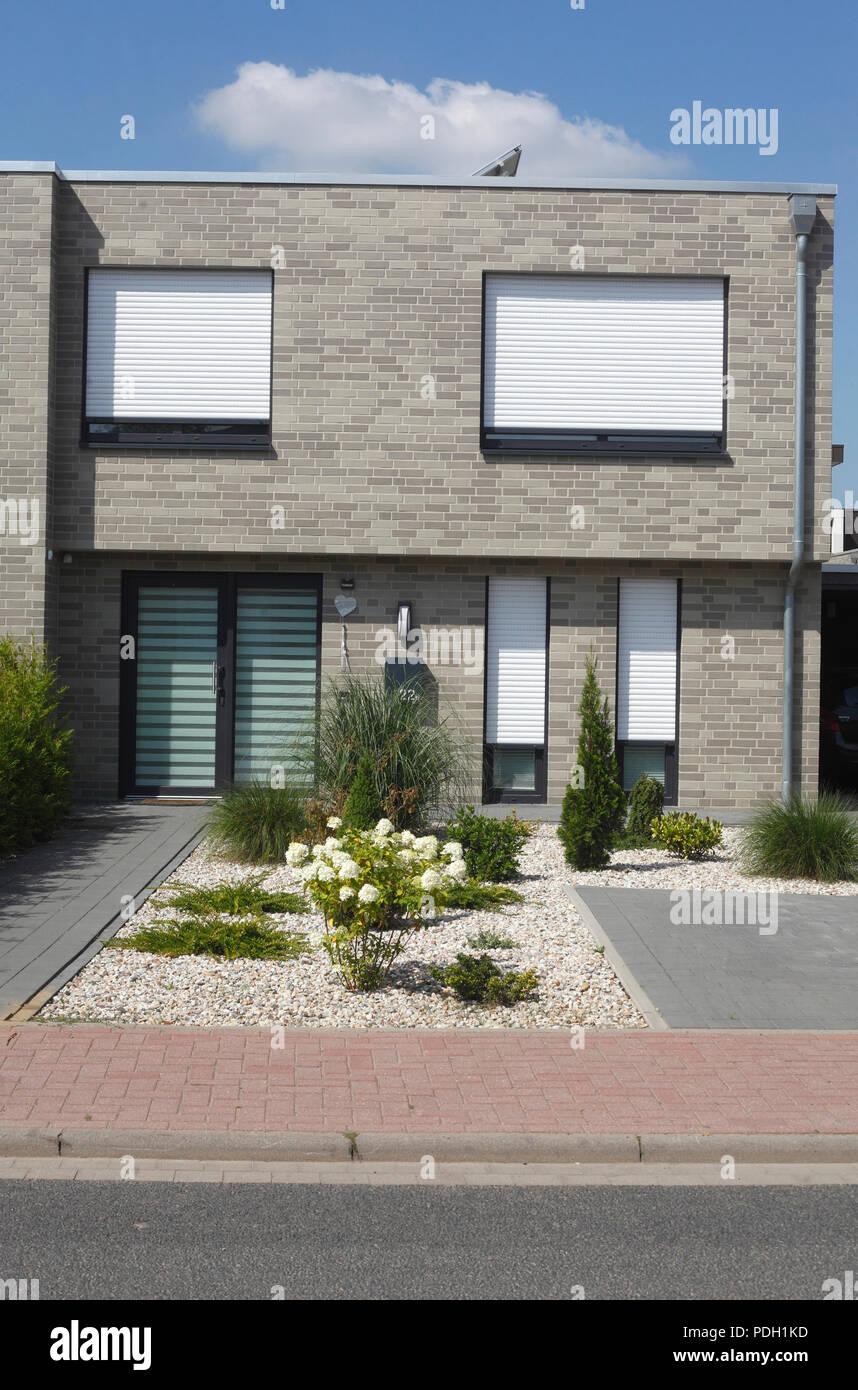Maison individuelle moderne de couleur grise, des fenêtres blanches ...
