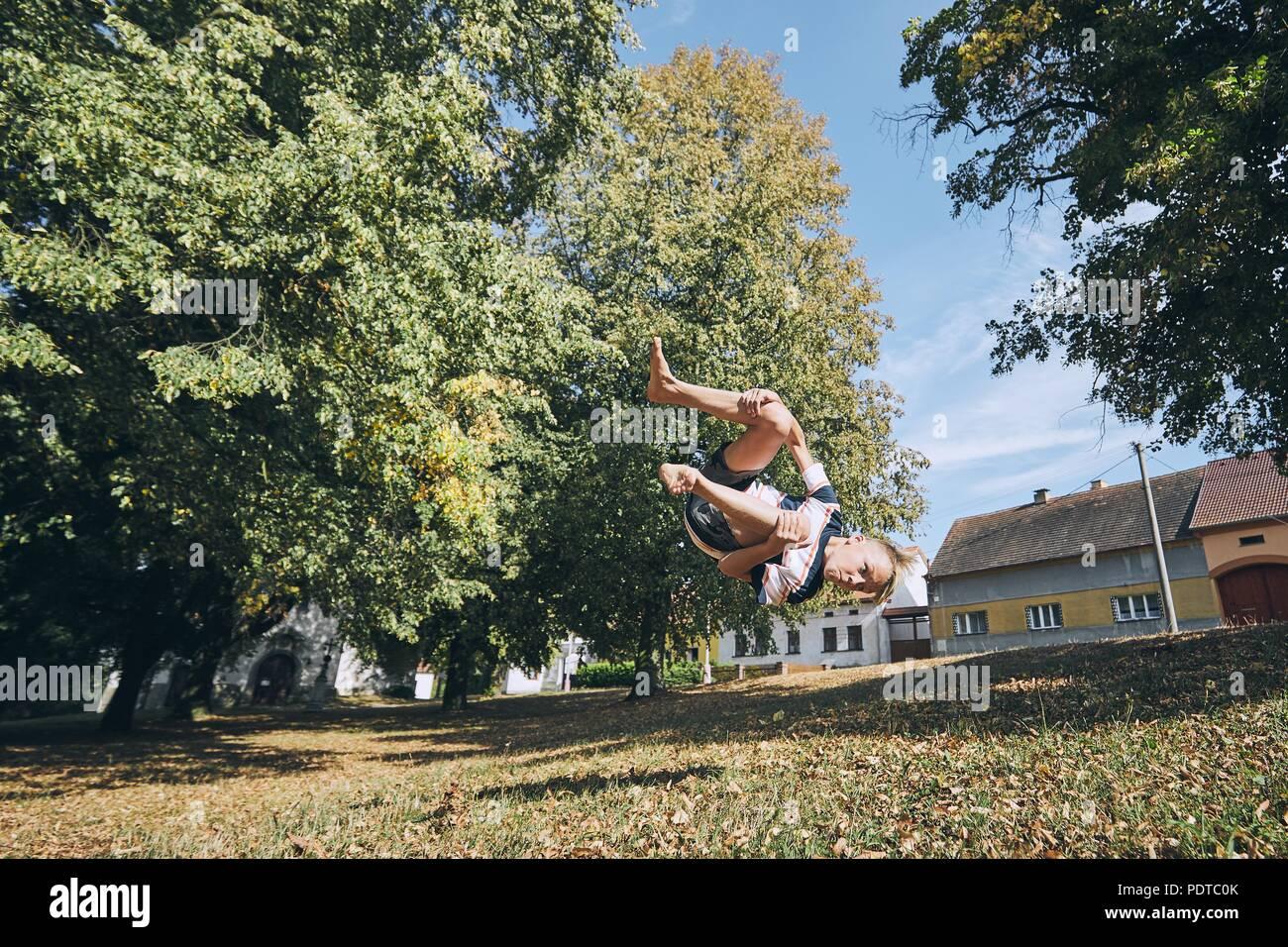 Boy practicing gratuitement runnuing en parc public et en sautant à l'envers. Photo Stock