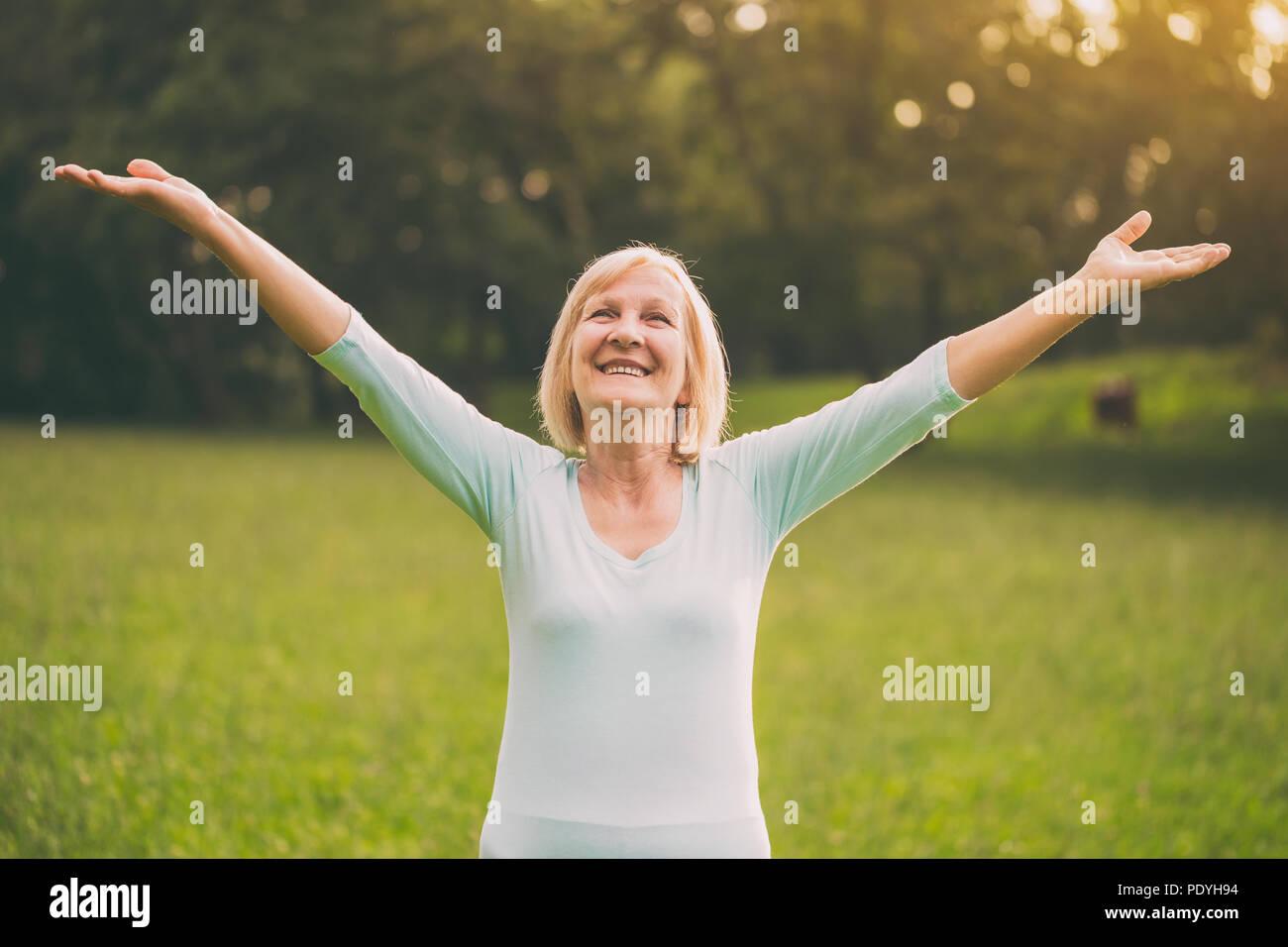 Senior woman entretient avec ses bras tendus dans la nature.Image est volontairement tonique. Photo Stock