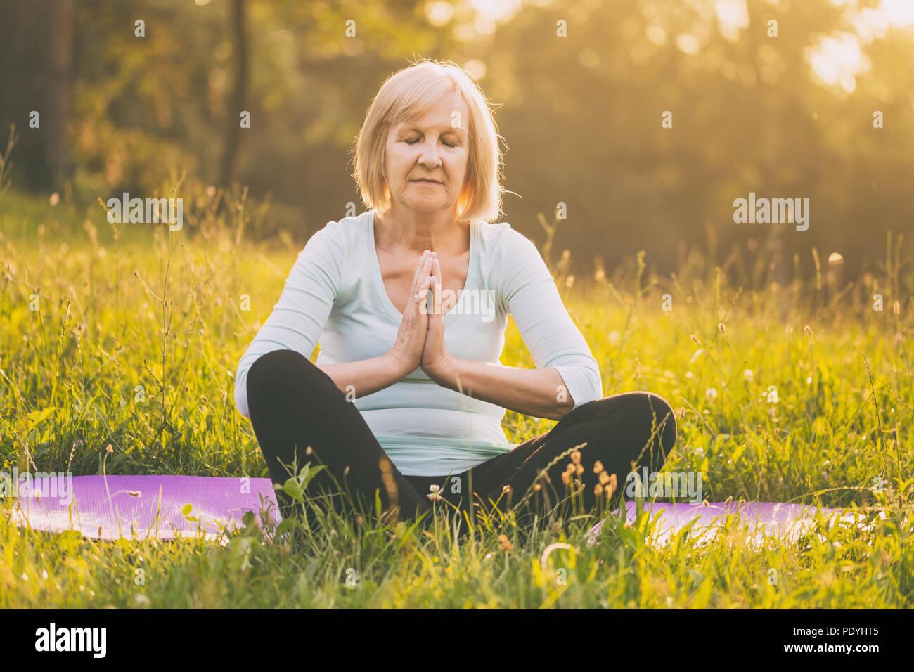 Senior woman bénéficie d'méditant dans la nature.Image est volontairement tonique. Photo Stock