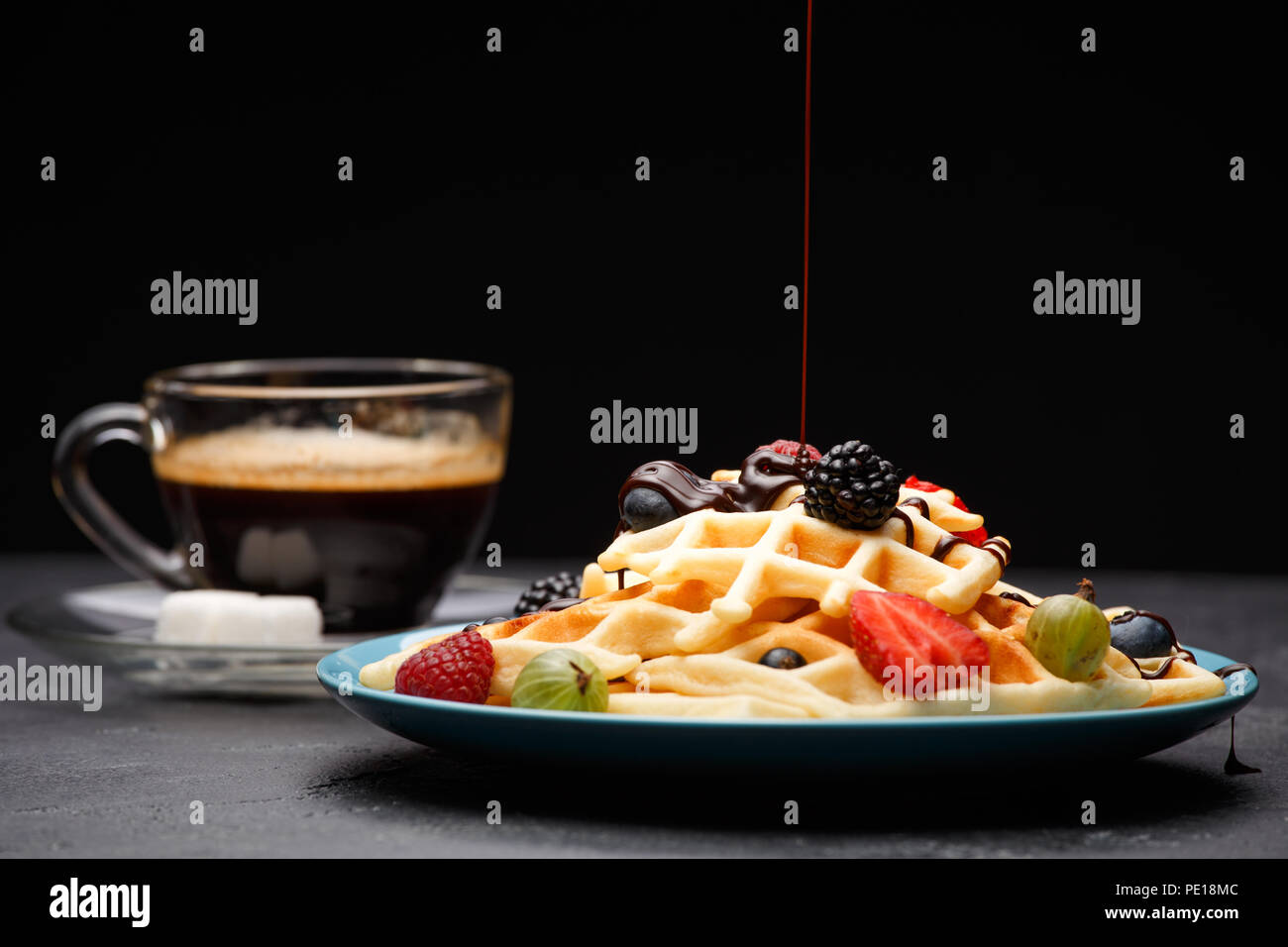 Photo de tasse de café noir avec du sucre avec des gaufres viennois avec fraises, framboises, groseilles et chocolat Photo Stock