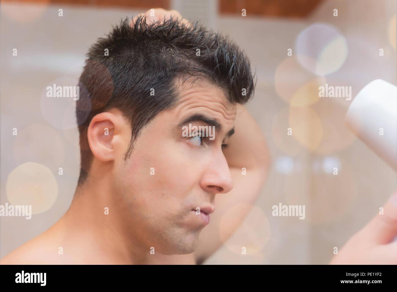 Bel homme en essuyant ses cheveux avec un sèche-cheveux. Concept Soins et Beauté de l'homme Photo Stock