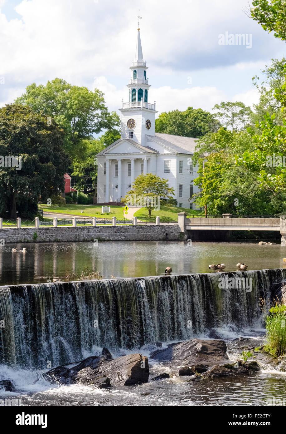 """Le livre blanc-columned Première Église unie du Christ avec l'horloge et son clocher date de 1824 et donne sur un lagon dans ce pittoresque scène de la Nouvelle-Angleterre dans le cœur historique de la Milford, Connecticut, USA. Maintenant pour s'identifier comme """"une petite ville avec un grand Cœur, il a été fondée en 1639 comme une colonie anglaise appelé Wepowage, le nom indien de la rivière qui coulait à travers la colonie. Un an plus tard, elle a été renommée Milford en référence à un moulin établi là. Photo Stock"""