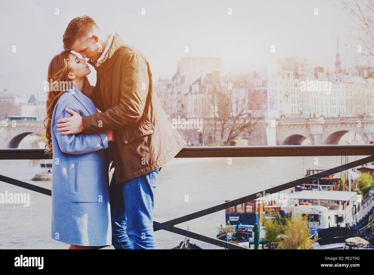 Amour couple dans la rue à Paris, moment romantique en lune de miel, happy young man and woman standing on pont sur Seine Banque D'Images