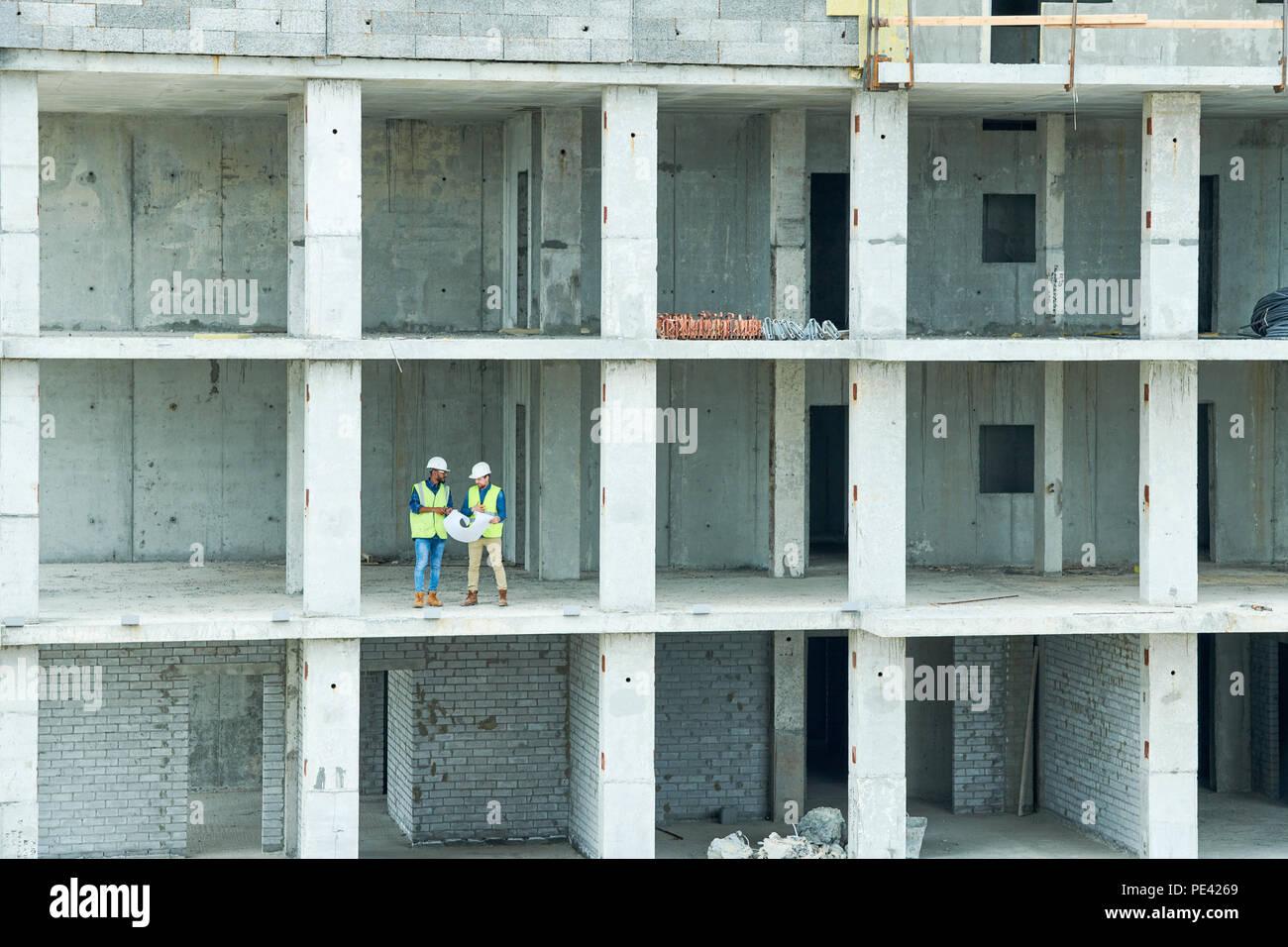 Les ingénieurs de construction en bâtiment inachevé Photo Stock