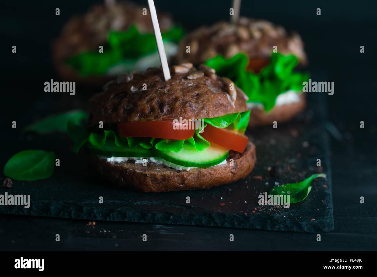 Sandwich avec salade verte, tomates, concombres et fromage à la crème sur le béton 24. Photo Stock