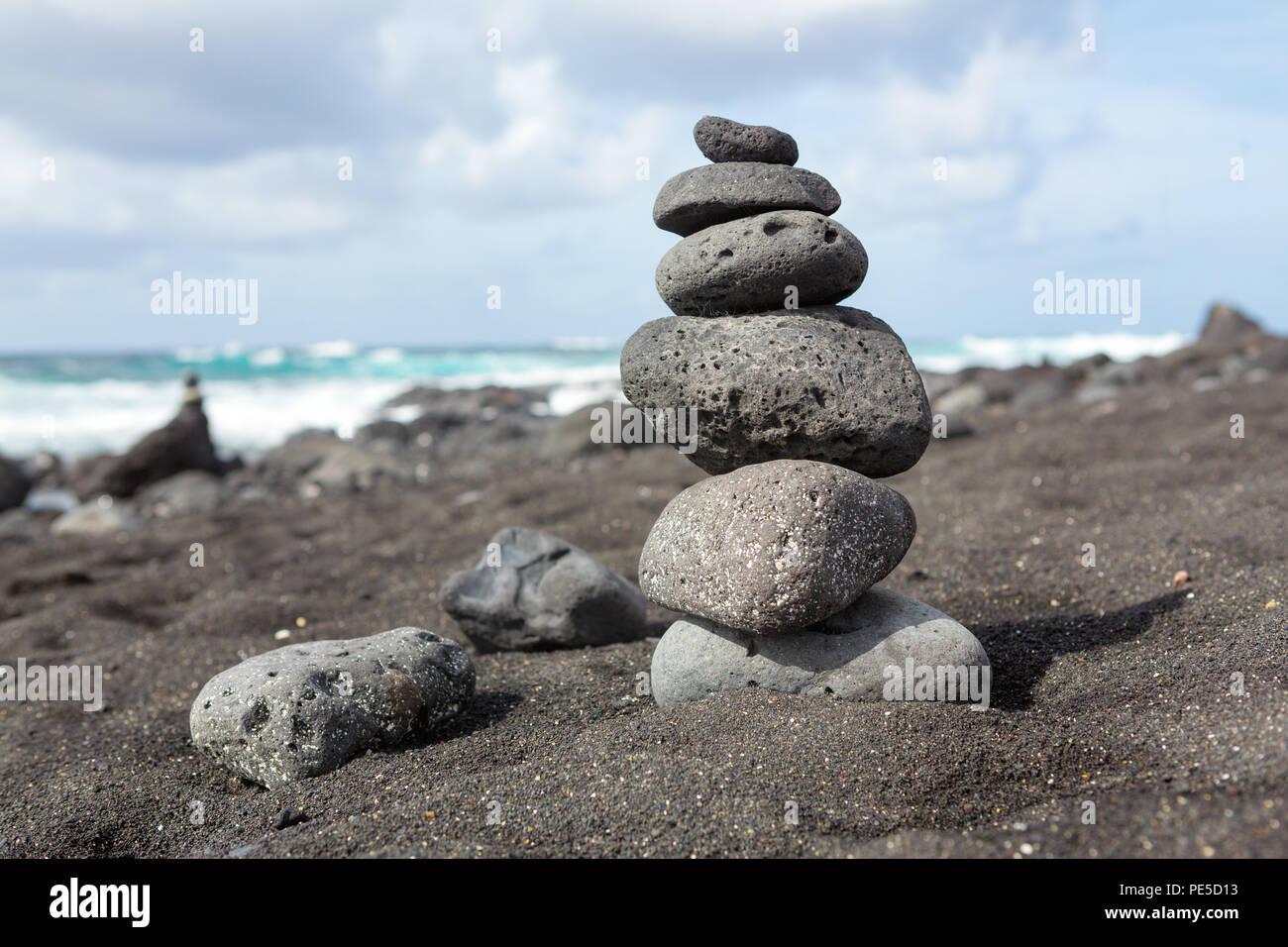 Des pierres empilées équilibré ou des cailloux sur une plage de sable noir. Photo Stock