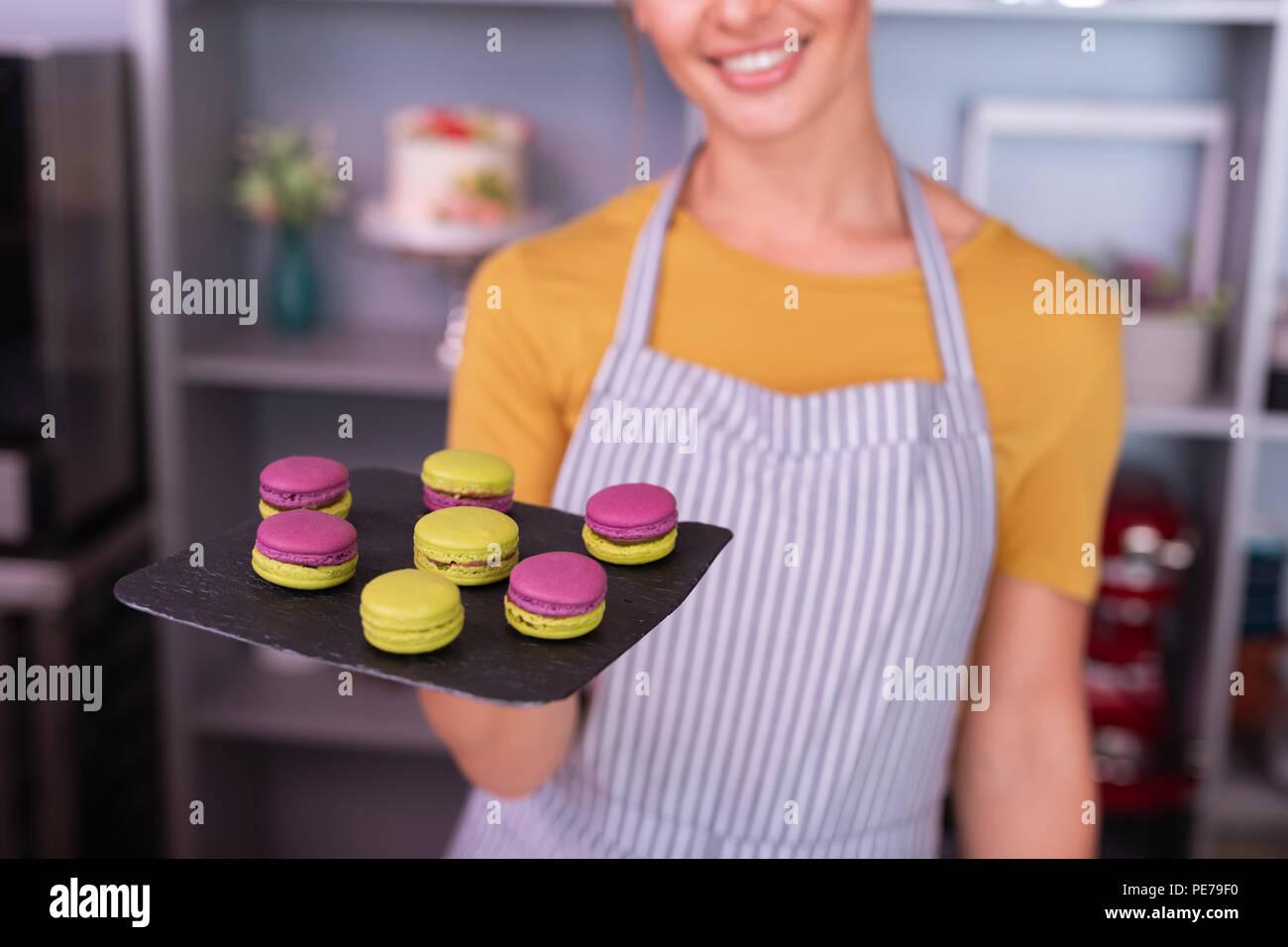 Young baker tout sourire après la cuisson des macarons Photo Stock
