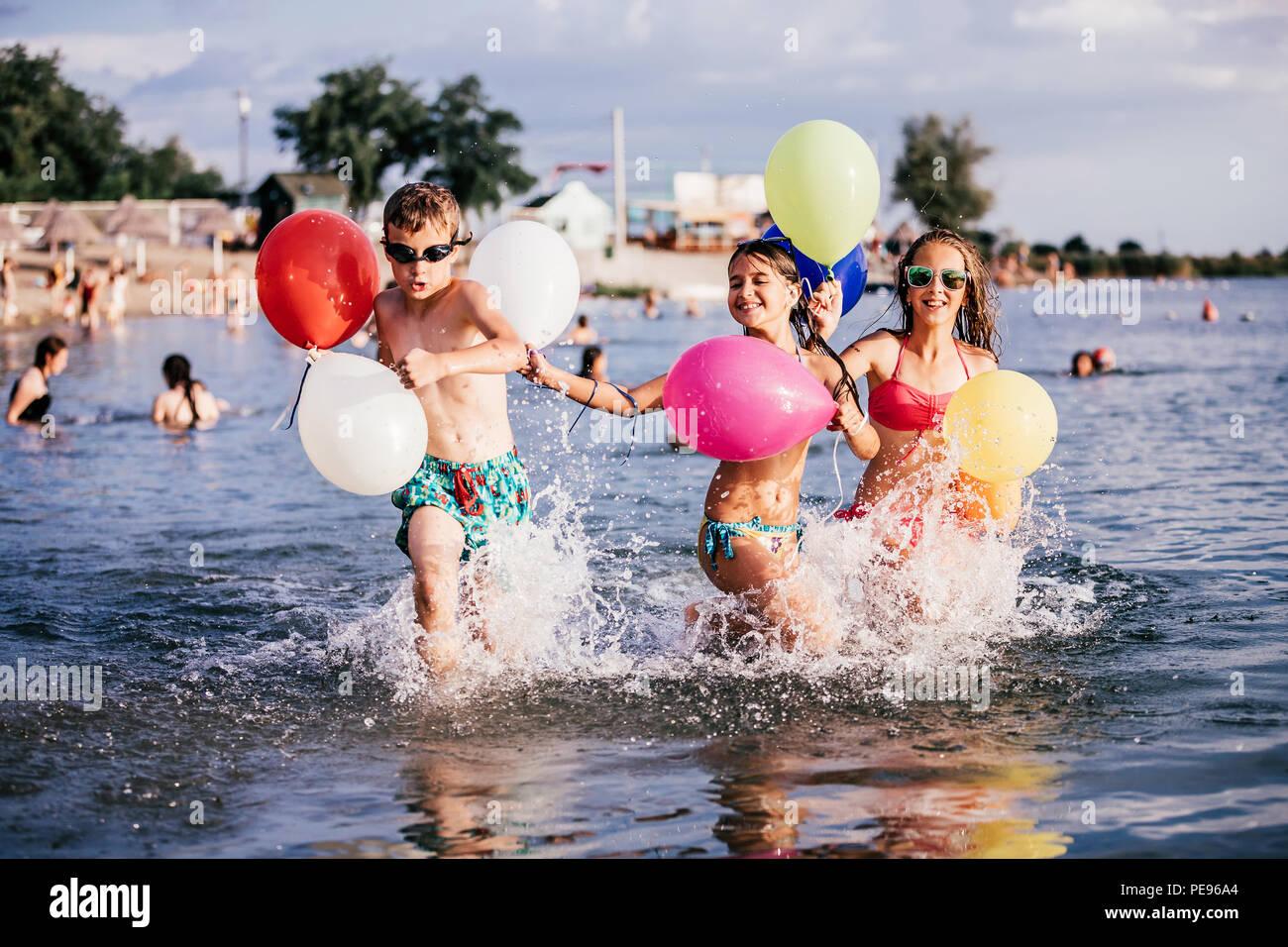 Heureux les enfants qui jouent avec des ballons dans la mer. Les enfants s'amuser en plein air. Vacances d'été et d'un style de vie sain concept Photo Stock