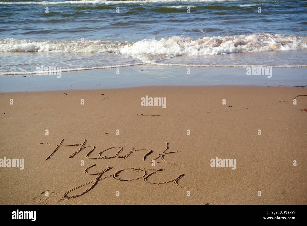 """Un beau message de remerciements """"merci"""" à la main sur le sable rouge sur une plage avec la mer bleue et une vague dans la partie supérieure, l'Île du Prince Édouard Photo Stock"""