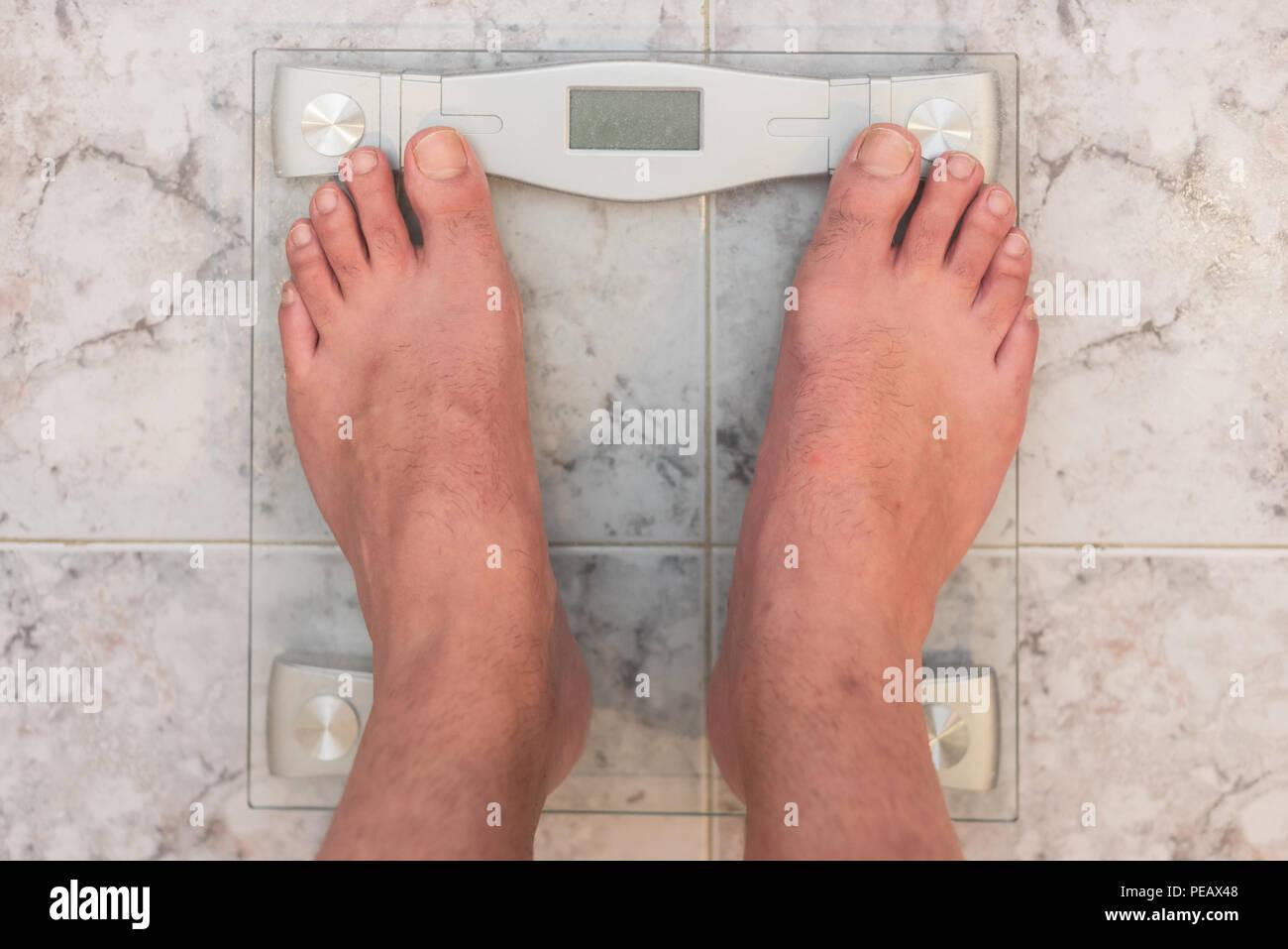 Pieds de l'homme debout sur l'échelle de poids Photo Stock