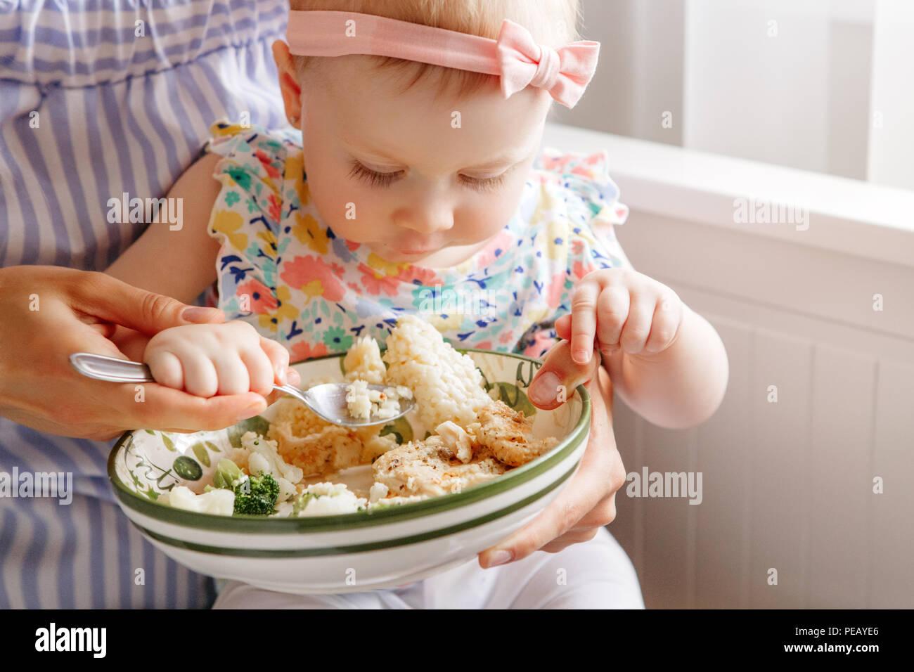 Closeup portrait of young woman mère nourrit sa fille fille avec légumes Brocoli Chou-fleur. Aliments biologiques sains pour les enfants. Natures mortes candide Banque D'Images