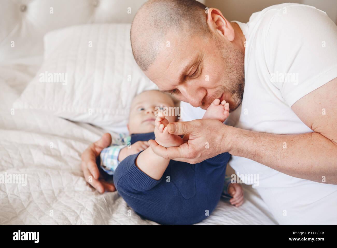Portrait touchant du moyen age woman in white t-shirt au lit avec bébé nouveau-né fils embrasser ses pieds orteils, parentalité enfance bondin Banque D'Images