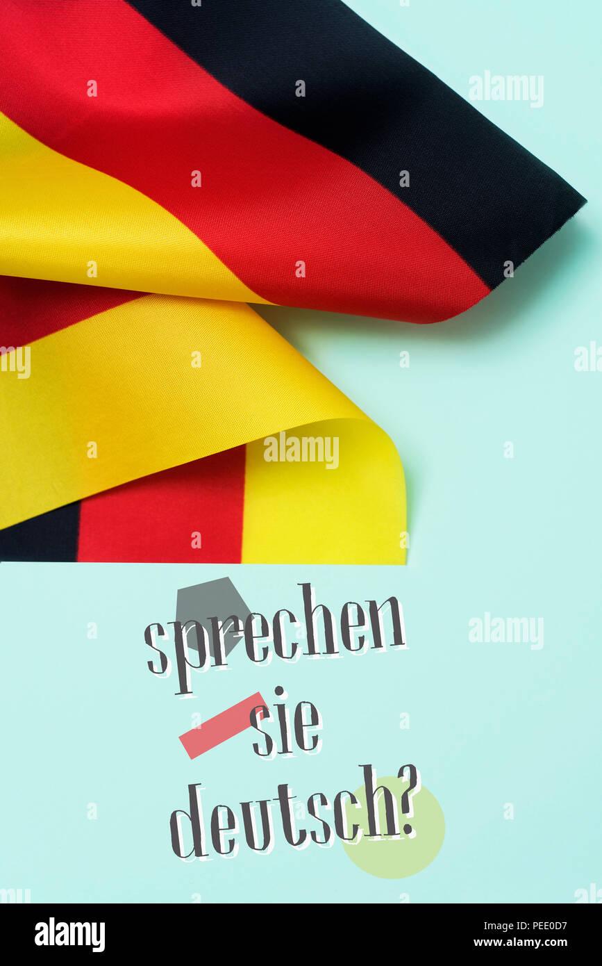 Quelques drapeaux de l'Allemagne et la question Sprechen Sie Deutsch? Parlez-vous allemand? Rédigé en allemand, sur un fond vert Photo Stock