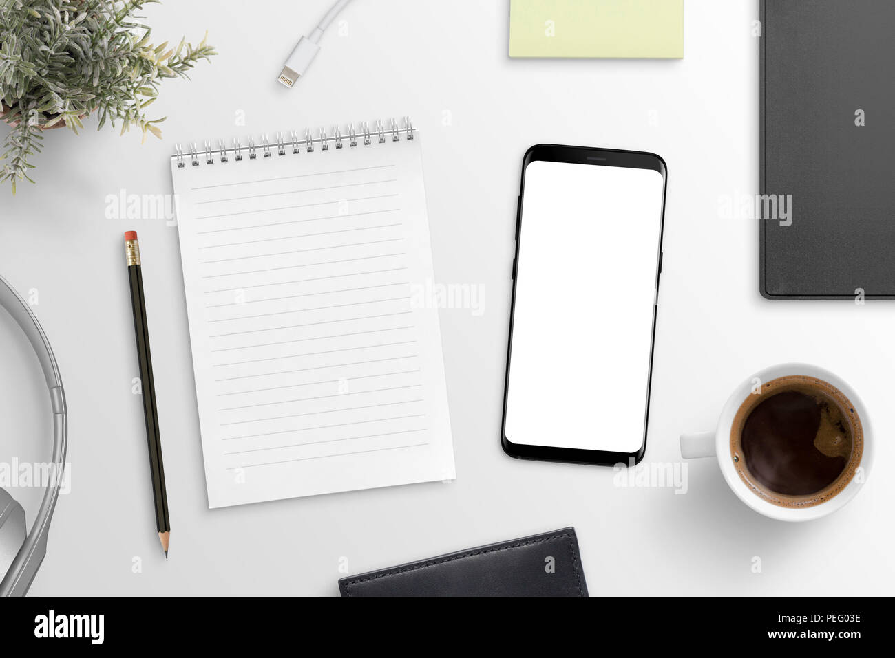 Le bloc notes vide et smart phone sur maquette moderne bureau