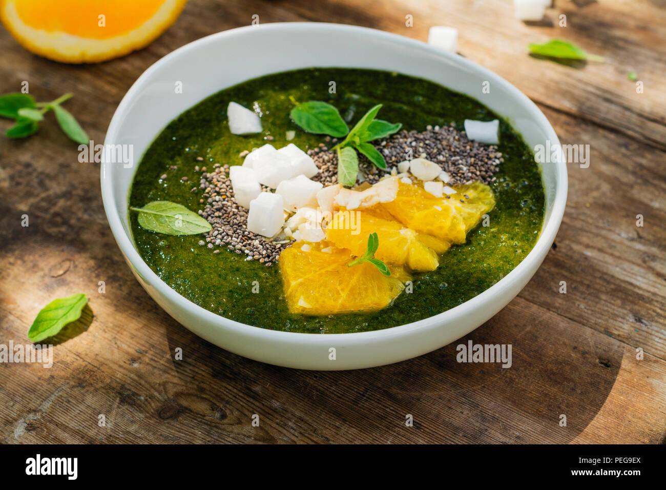 Bol avec banana smoothie vert, les épinards, les oranges et les graines de chia Photo Stock
