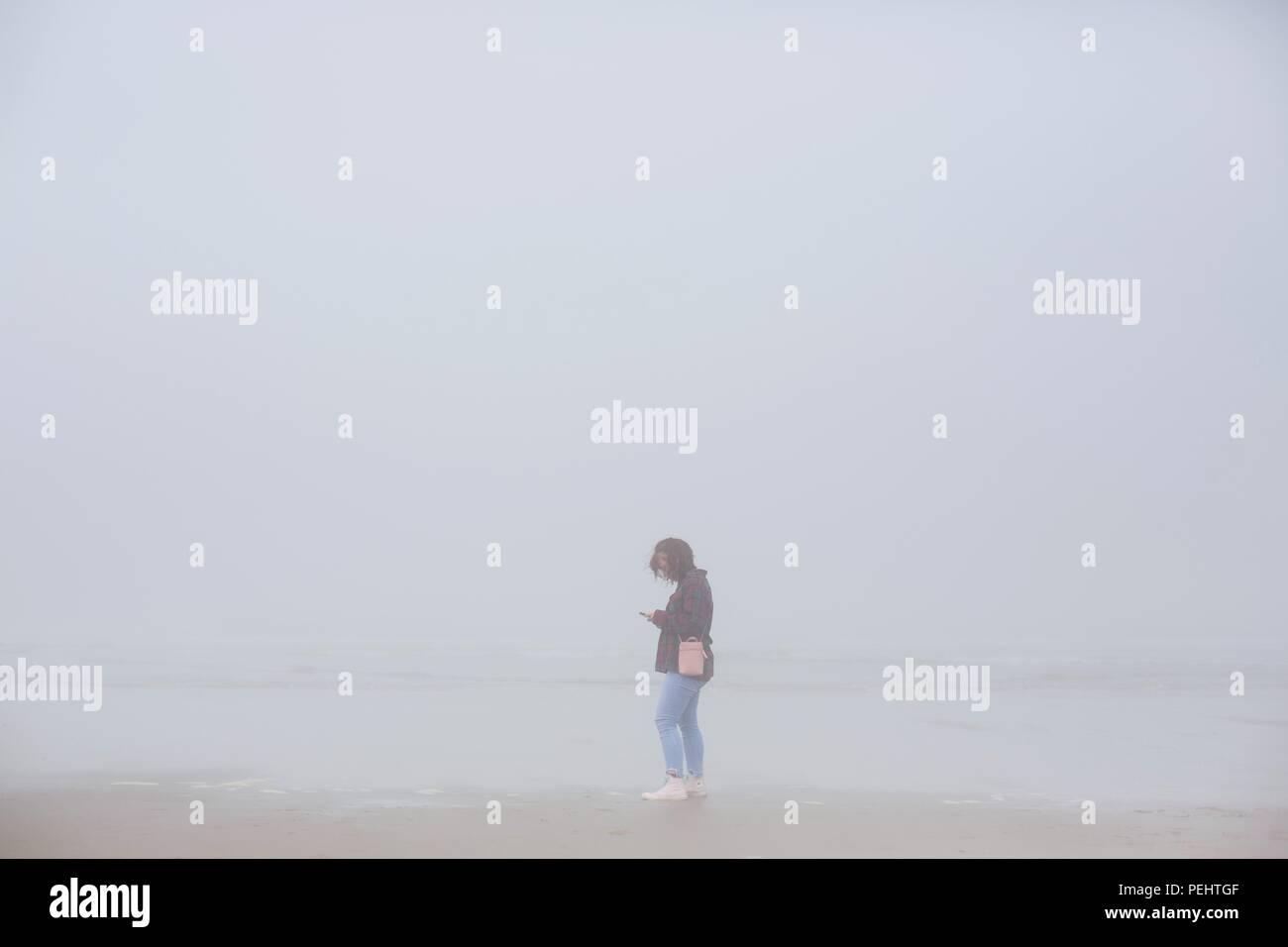 Une jeune femme à la recherche à son téléphone en étant debout sur une plage de brouillard près de Florence, Oregon, USA. Photo Stock