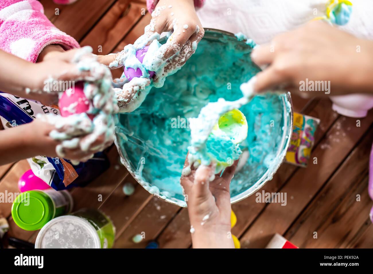 Un groupe de jeunes filles, des enfants faire un désordre avec écume de slime Photo Stock