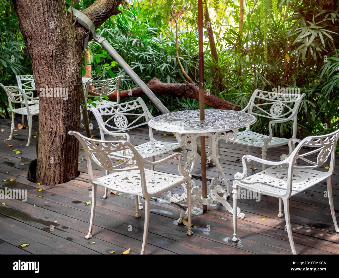 Vintage blanc table en acier fixé sur un plancher en bois et arbres ...