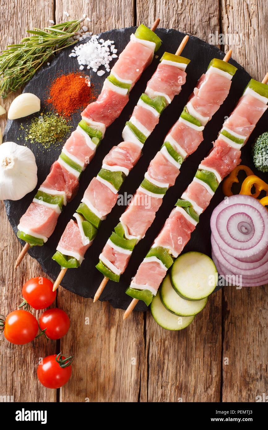 Matières shish kebab au poivre vert sur les brochettes, close-up et de légumes, d'herbes sur la table. Haut Vertical Vue de dessus Photo Stock