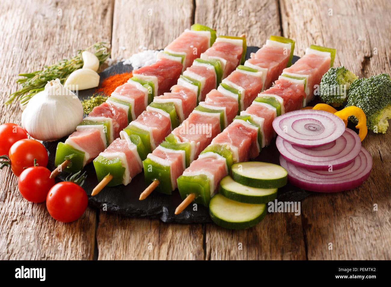 Close up des brochettes avec la viande et les légumes juteux. Kebab de viande de porc crue close-up. Rustique, horizontale Photo Stock