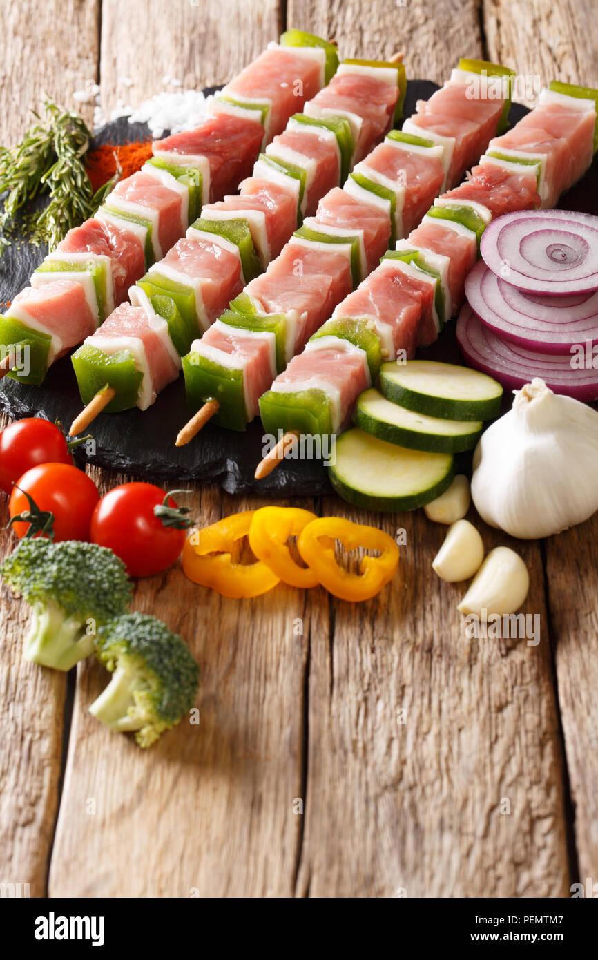 Préparé cru mariné porc shish kebab avec du poivre sur les brochettes, close-up et les ingrédients, légumes, épices, fines herbes sur la table verticale. Photo Stock