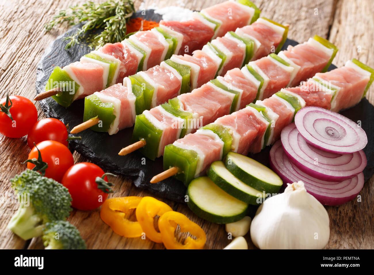 Préparation d'un barbecue: matières shish kebab au poivre vert sur les brochettes, close-up et de légumes, d'herbes sur la table horizontale. Photo Stock