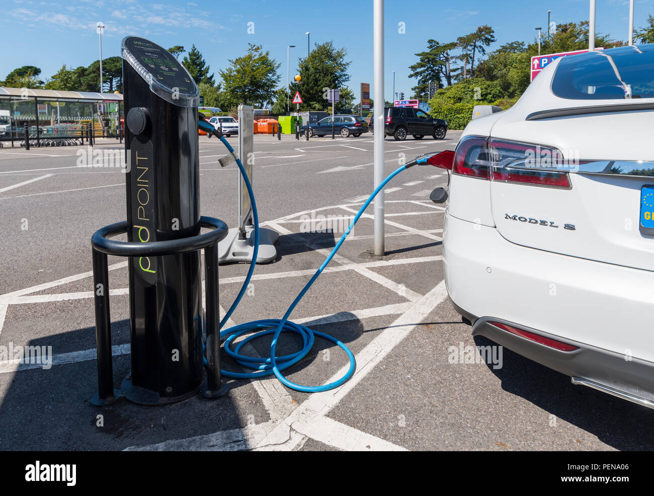 Voiture électrique branché sur un point de recharge. Véhicule électrique connecté à un port de charge dans le West Sussex, Angleterre, Royaume-Uni. Photo Stock