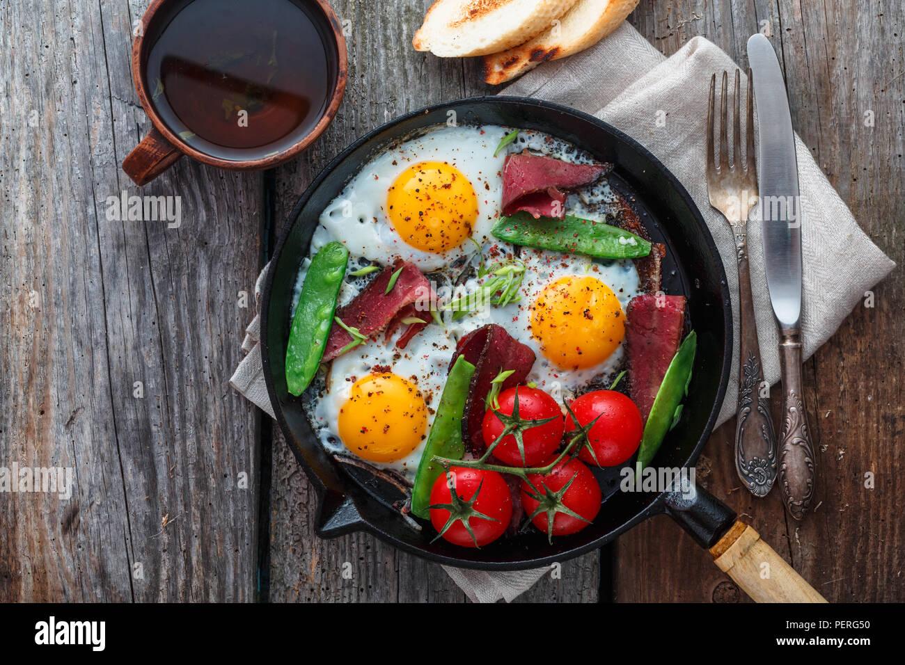 Oeufs frits dans une poêle avec les tomates cerises, les pois verts et le pastrami. Copyspace Banque D'Images