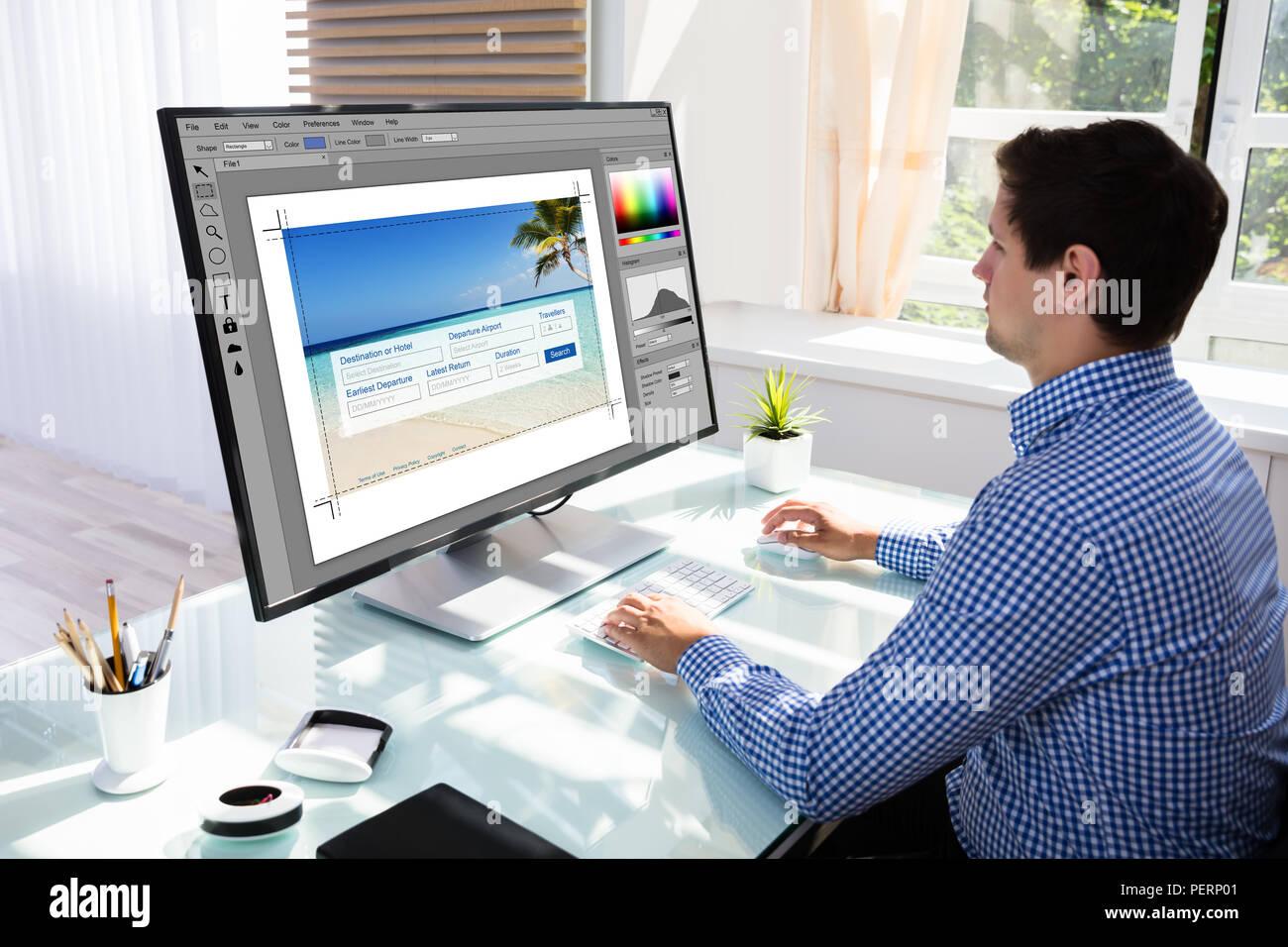 Jeune homme designer édition de photos sur computer in office Photo Stock