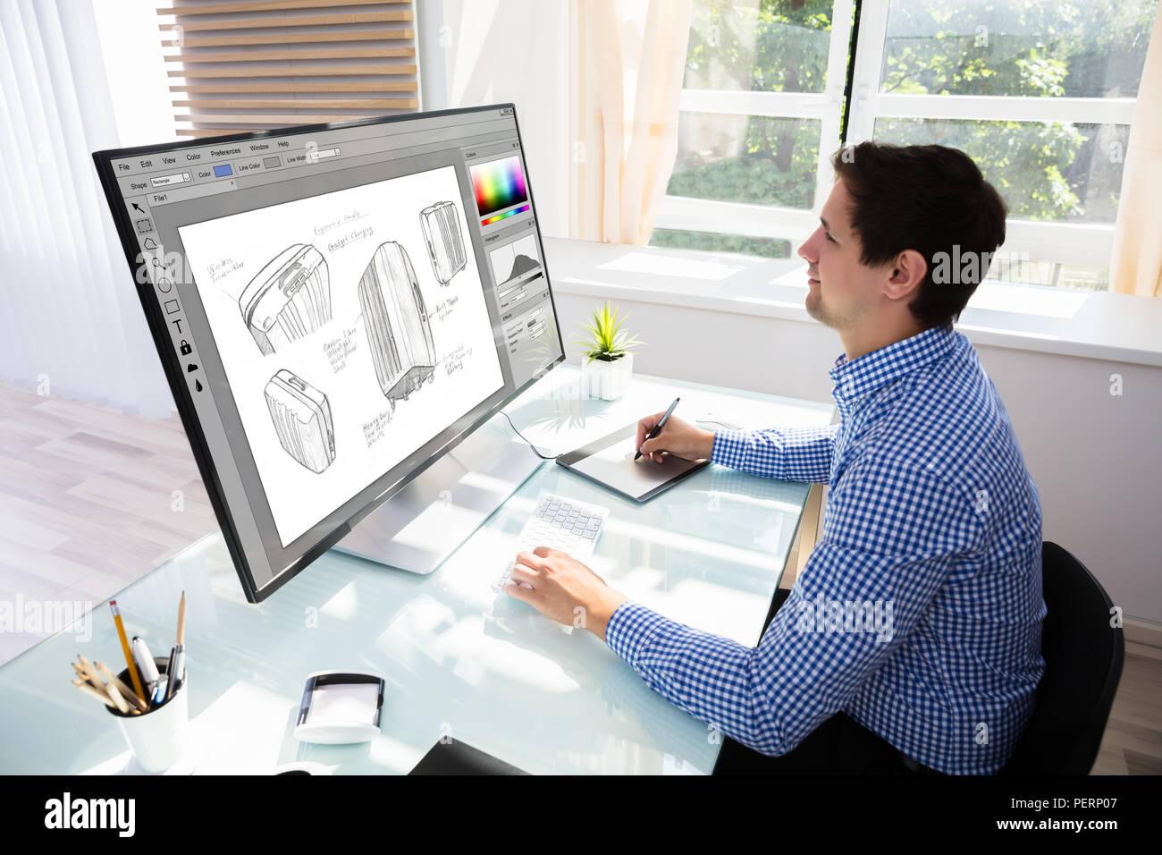 Vue latérale d'un jeune designer Dimensions valise sur ordinateur à l'aide de tablette graphique Photo Stock