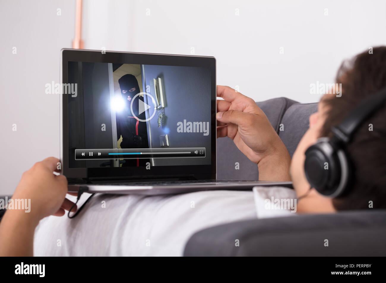 Portrait d'un homme regardant thriller film sur ordinateur portable Photo Stock