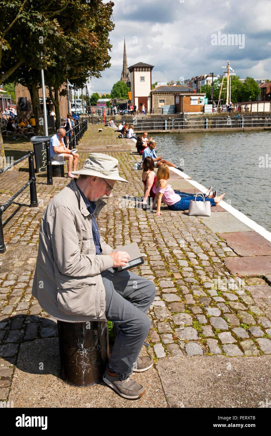 Royaume-uni, Angleterre, Bristol, port, Man reading kindle e-reader sur le quai à l'extérieur de la galerie Arnolfini Photo Stock