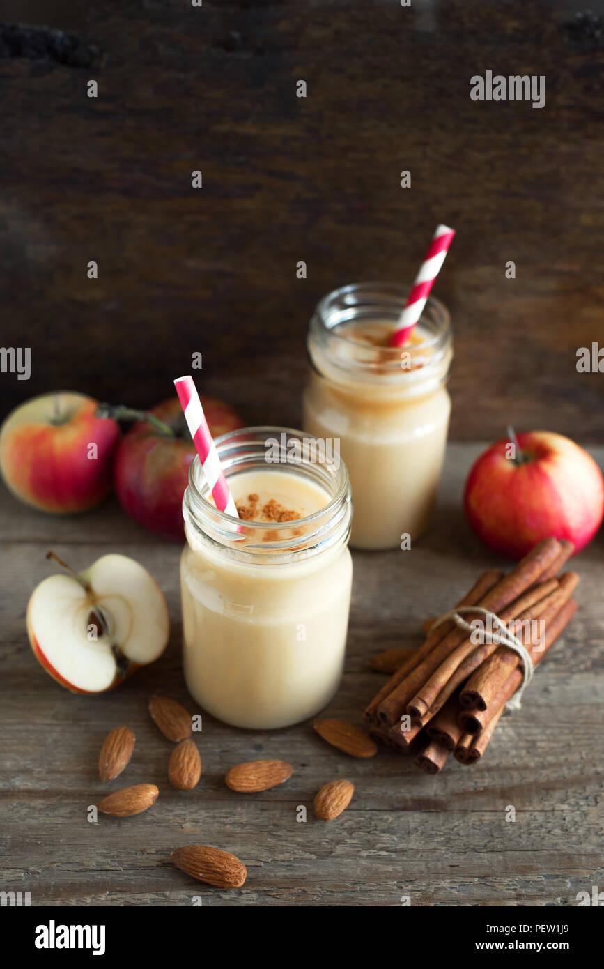 Apple pie smoothie boisson avec protéines de lait d'amande. Smoothie aux pommes maison avec apple pie épices (cannelle) sur fond de bois, copie de l'espace. Photo Stock