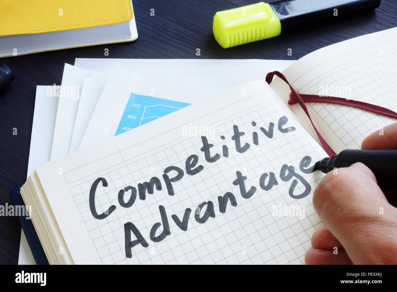 L'homme est écrit mots avantage concurrentiel dans le bloc-notes. Photo Stock