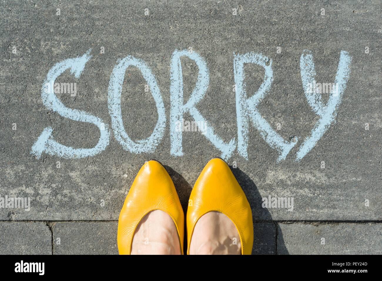 Pieds femelles avec texte désolé écrit sur l'asphalte gris Photo Stock