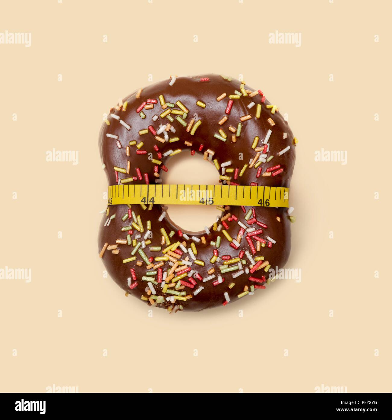 Suivre un régime, conceptual image. Beignet au chocolat avec du sucre et ruban à mesurer, studio shot. Photo Stock