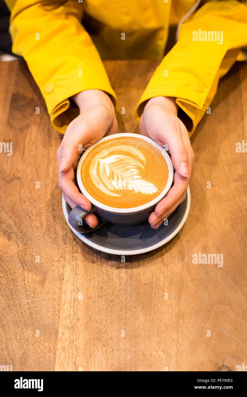 Les mains tenant une latte sur une table en bois. Photo Stock