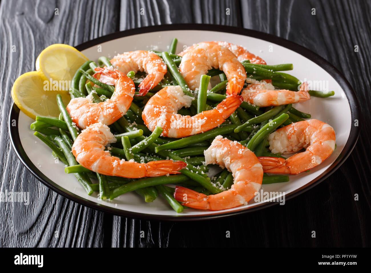 Les aliments biologiques, salade verte avec crevettes: haricots, fromage et citron close-up sur une plaque sur une table horizontale. Photo Stock