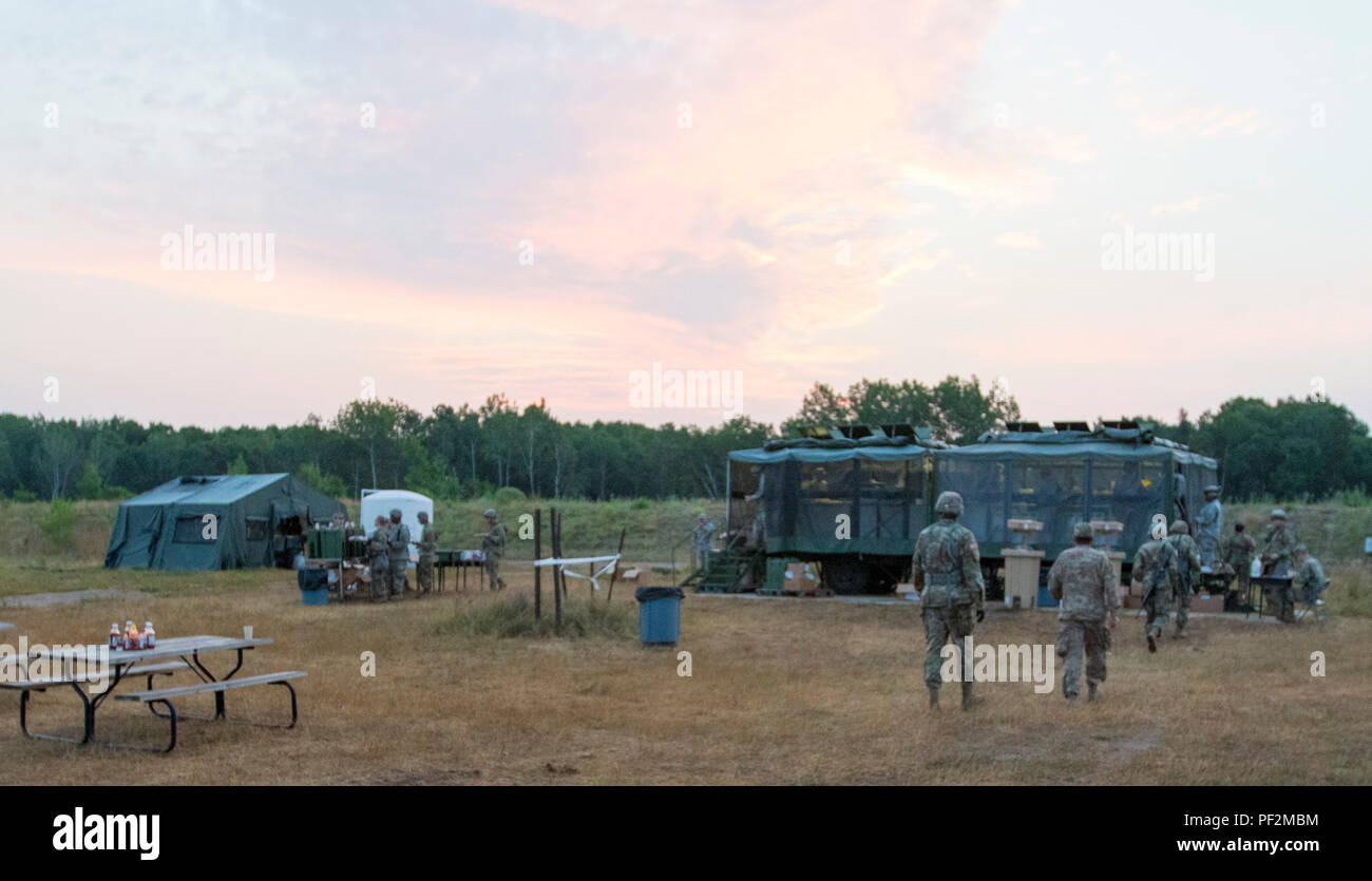 Des soldats venus manger un petit-déjeuner au lever du soleil, à partir de la remorque cuisine recevez, arrière-plan, le Camp Ripley, Minn., 15 août 2018. Les cuisines sont en mesure de faire cuire la nourriture et le service des repas en cours de l'installation dans une seule journée. (U.S. Réserve de l'armée photo prise par le s.. Adam Decker) Photo Stock